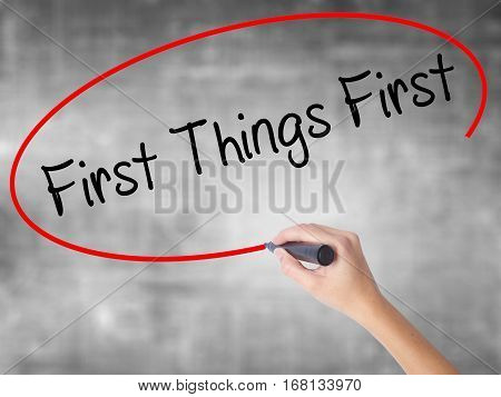Woman Hand Writing First Things First With Black Marker Over Transparent Board