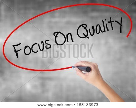 Woman Hand Writing Focus On Quality With Black Marker Over Transparent Board