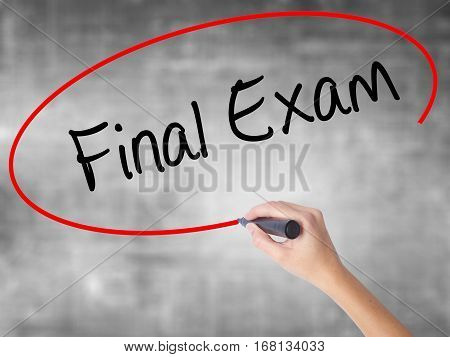 Woman Hand Writing Final Exam With Black Marker Over Transparent Board