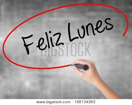 Woman Hand Writing Feliz Lunes (happy Monday In Spanish) With Black Marker Over Transparent Board