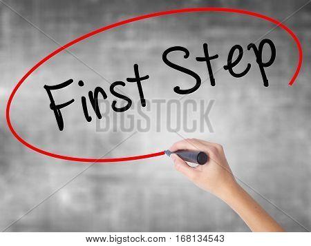 Woman Hand Writing First Step  With Black Marker Over Transparent Board