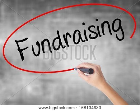 Woman Hand Writing Fundraising With Black Marker Over Transparent Board