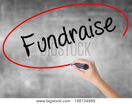 Woman Hand Writing Fundraise With Black Marker Over Transparent Board