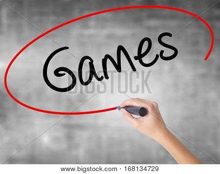 Woman Hand Writing Games With Black Marker Over Transparent Board