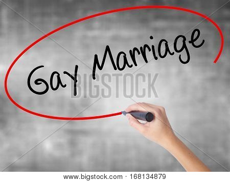 Woman Hand Writing Gay Marriage With Black Marker Over Transparent Board.