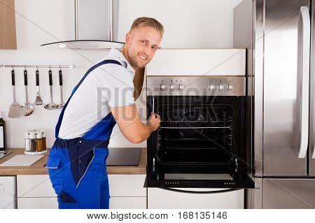 Young Male Technician Repairing Oven In Kitchen