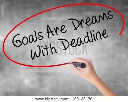 Woman Hand Writing Goals Are Dreams With Deadline With Black Marker Over Transparent Board