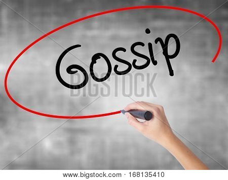 Woman Hand Writing Gossip With Black Marker Over Transparent Board