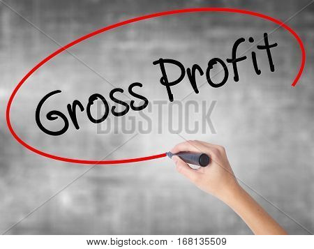 Woman Hand Writing Gross Profit With Black Marker Over Transparent Board