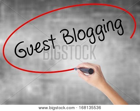 Woman Hand Writing Guest Blogging  With Black Marker Over Transparent Board
