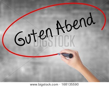 Woman Hand Writing Guten Abend  (good Evening In German) With Black Marker Over Transparent Board