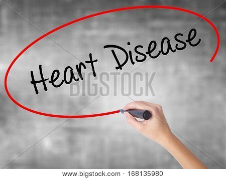 Woman Hand Writing Heart Disease With Black Marker Over Transparent Board
