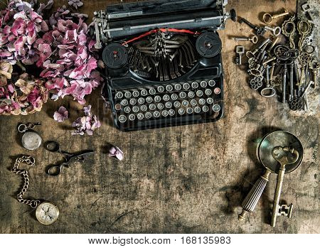 Vintage typewriter hortensia flowers and old keys on wooden table. Nostalgic still life