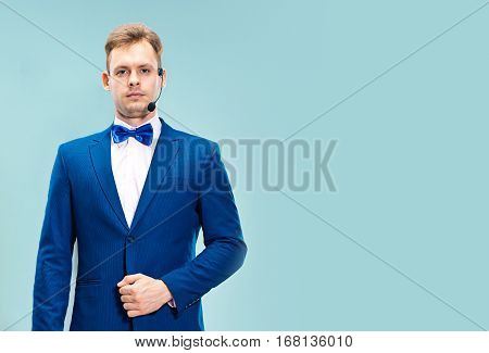 Portrait of a handsome customer service operator wearing a headset isolated on blue studio background