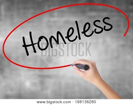 Woman Hand Writing Homeless With Black Marker Over Transparent Board.