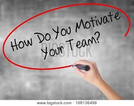 Woman Hand Writing How Do You Motivate Your Team? With Black Marker Over Transparent Board