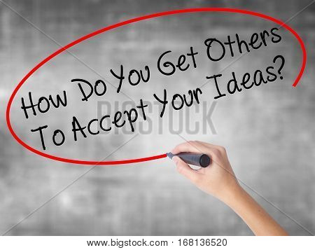 Woman Hand Writing How Do You Get Others To Accept Your Ideas? With Black Marker Over Transparent Bo