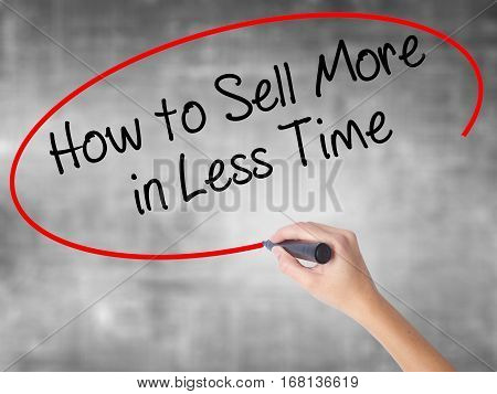 Woman Hand Writing How To Sell More In Less Time With Black Marker Over Transparent Board.
