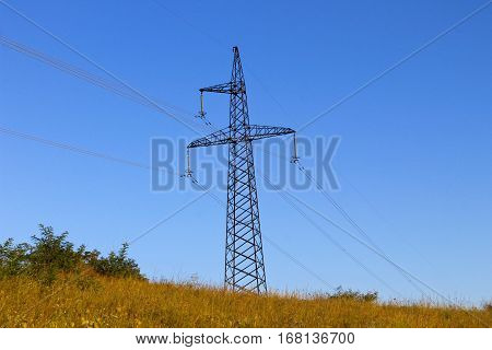 High voltage power tower against blue sky