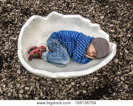 Kid cuddling in an eggshell and wearing a cap