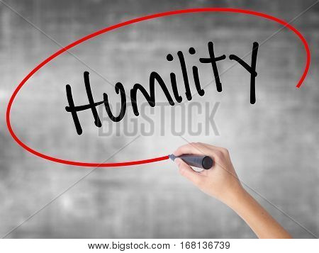 Woman Hand Writing Humility  With Black Marker Over Transparent Board.