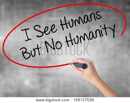 Woman Hand Writing I See Humans But No Humanity With Black Marker Over Transparent Board.