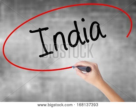 Woman Hand Writing India With Black Marker Over Transparent Board.