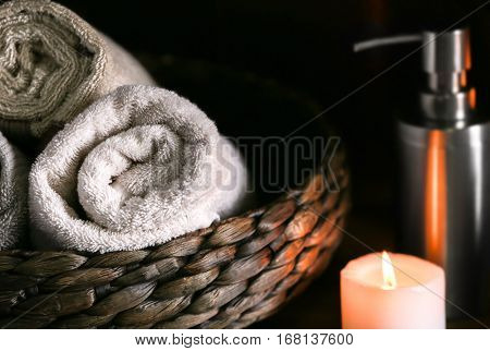 Towels in wicker basket and burning candle, closeup