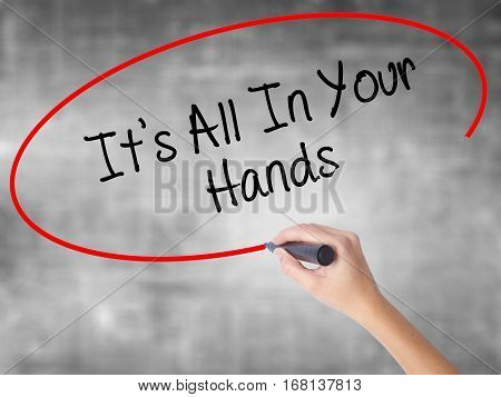 Woman Hand Writing It's All In Your Hands  With Black Marker Over Transparent Board.