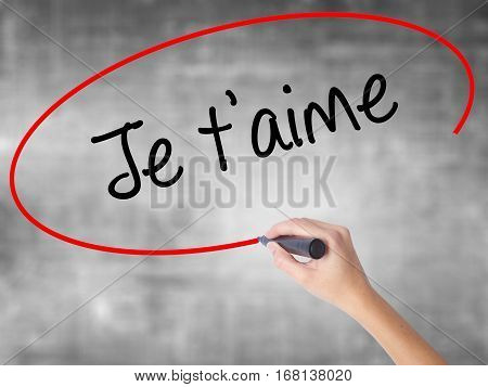 Woman Hand Writing Je T'aime ( I Love You In French)  With Black Marker Over Transparent Board