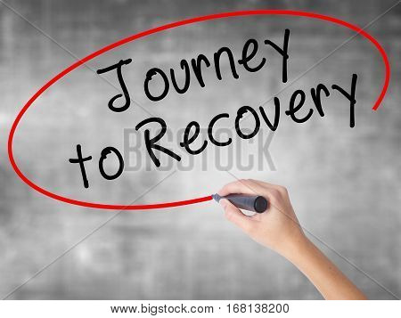 Woman Hand Writing Journey To Recovery With Black Marker Over Transparent Board