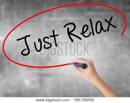 Woman Hand Writing Just Relax With Black Marker Over Transparent Board
