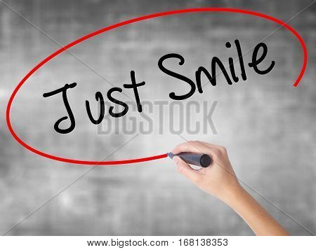 Woman Hand Writing Just Smile With Black Marker Over Transparent Board
