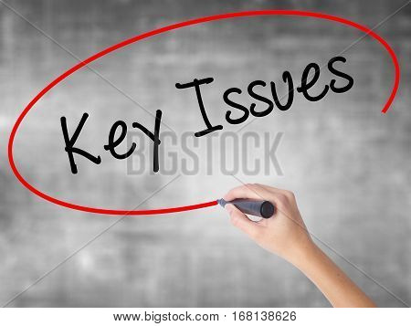 Woman Hand Writing Key Issues With Black Marker Over Transparent Board