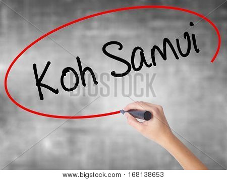 Woman Hand Writing Koh Samui With Black Marker Over Transparent Board