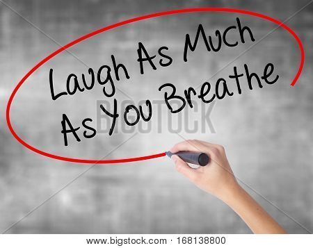 Woman Hand Writing Laugh As Much As You Breathe With Black Marker Over Transparent Board.
