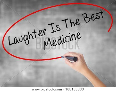 Woman Hand Writing Laughter Is The Best Medicine  With Black Marker Over Transparent Board