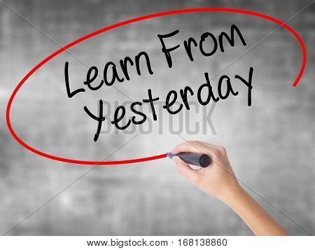 Woman Hand Writing Learn From Yesterday With Black Marker Over Transparent Board