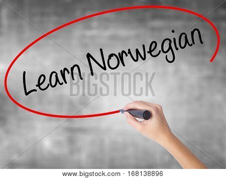 Woman Hand Writing Learn Norwegian With Black Marker Over Transparent Board.