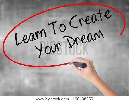 Woman Hand Writing Learn To Create Your Dream With Black Marker Over Transparent Board