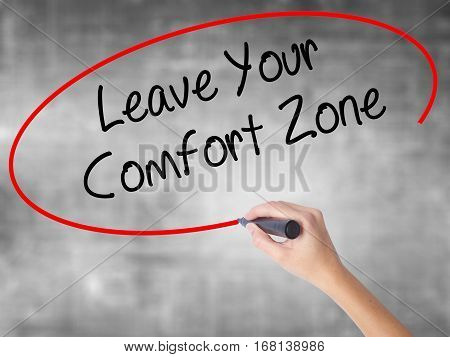 Woman Hand Writing Leave Your Comfort Zone With Black Marker Over Transparent Board