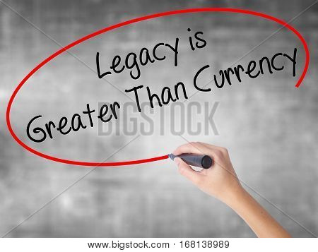 Woman Hand Writing Legacy Is Greater Than Currency With Black Marker Over Transparent Board