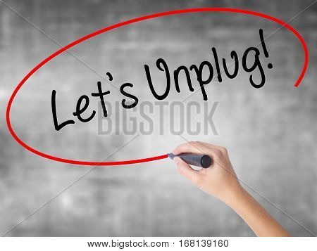 Woman Hand Writing Let's Unplug! With Black Marker Over Transparent Board