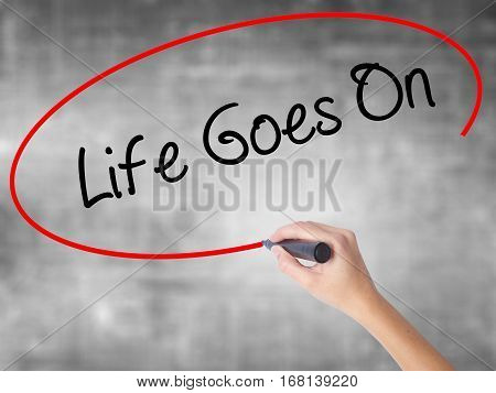 Woman Hand Writing Life Goes On With Black Marker Over Transparent Board