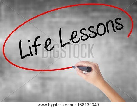 Woman Hand Writing Life Lessons With Black Marker Over Transparent Board