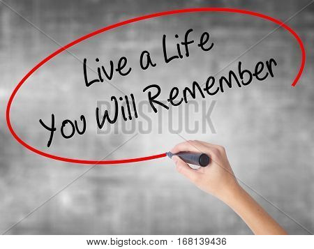 Woman Hand Writing Live A Life You Will Remember With Black Marker Over Transparent Board