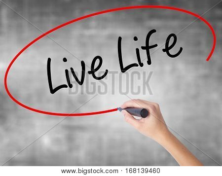 Woman Hand Writing Live Life With Black Marker Over Transparent Board
