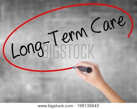 Woman Hand Writing Long-term Care With Black Marker Over Transparent Board