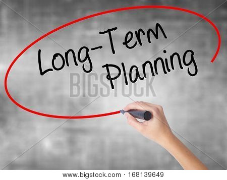Woman Hand Writing  Long-term Planning With Black Marker Over Transparent Board
