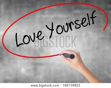 Woman Hand Writing Love Yourself With Black Marker Over Transparent Board